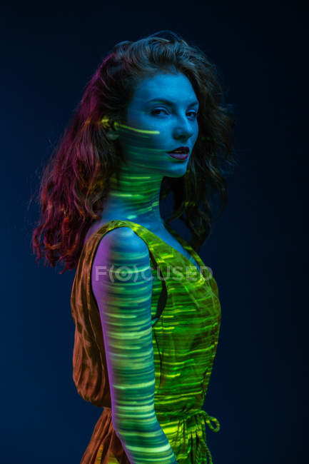 Portrait of elegant sensual woman standing in stripes of warm light — Stock Photo