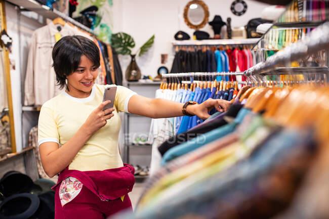 Красивая молодая женщина улыбается и использует смартфон, чтобы сфотографировать одежду на рельсах, стоя в маленьком магазине — стоковое фото