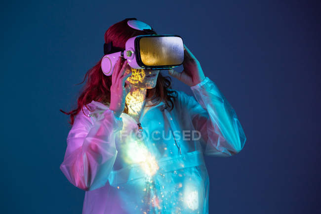 Woman using VR glasses in neon light on blue background — Stock Photo