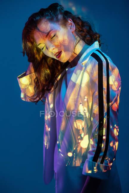 Mujer soñadora con los ojos cerrados posando en luz de neón - foto de stock