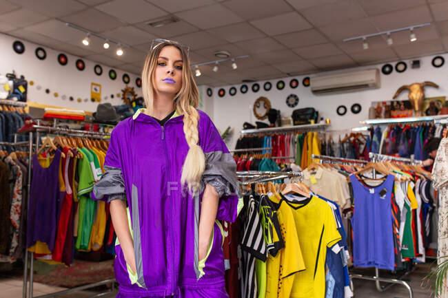 Красива молода жінка в яскравому моді, тримаючи руки в кишенях і дивлячись на камеру, стоячи біля залізничного одягу в маленькому магазині. — стокове фото