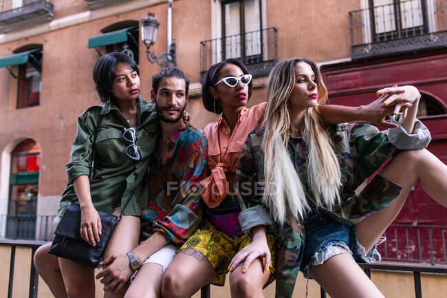 Groupe de jeunes en tenue tendance assis sur une clôture dans la rue de la ville et regardant ailleurs — Photo de stock