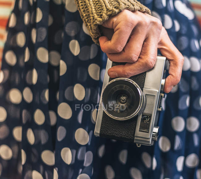 Hand of woman holding vintage camera against patterned colorful wall — Stock Photo