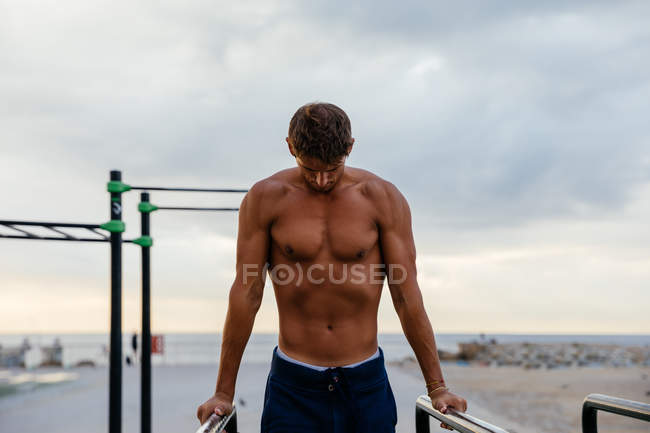 A male athlete works out in a outside gym — Stock Photo