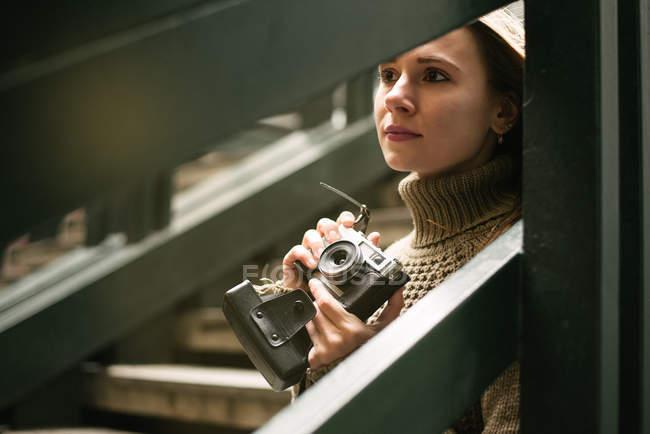 Вдумчивая молодая женщина держит винтажную камеру, опираясь на перила лестницы — стоковое фото