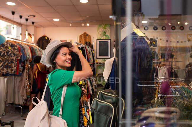 Веселая женщина выбирает одежду в магазине — стоковое фото