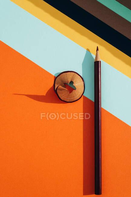 Crayon et copeaux d'affûtage, sur fond de papiers rayés colorés. Concept de retour à l'école — Photo de stock