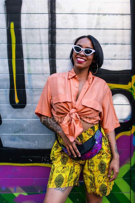 Vista lateral da jovem fêmea atraente na roupa da moda rindo e acenando a mão enquanto estava perto da parede de grafite brilhante na rua da cidade — Fotografia de Stock