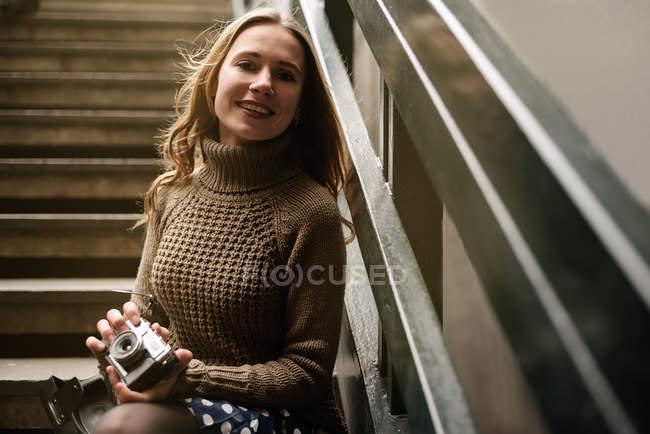 Ritratto di felice giovane donna in possesso di fotocamera vintage mentre appoggiato su ringhiera scala — Foto stock