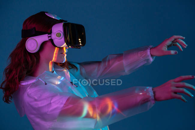 Mujer tocando el aire en gafas VR en luz de neón - foto de stock