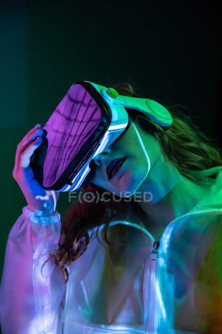 Женщина в VR очках в неоновом свете — стоковое фото