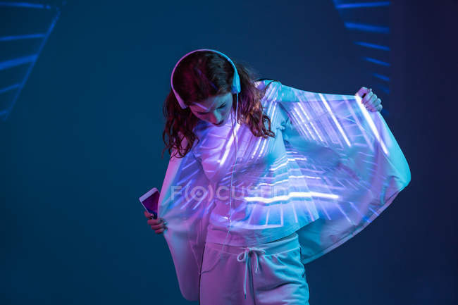 Young woman in headphones looking at neon light projection on blazer — Stock Photo