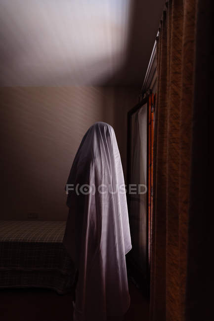 Person disguised as ghost for Halloween walking in house — Stock Photo