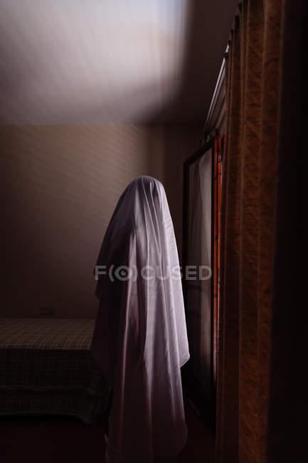 Personne déguisé en fantôme pour Halloween à pied dans la maison — Photo de stock