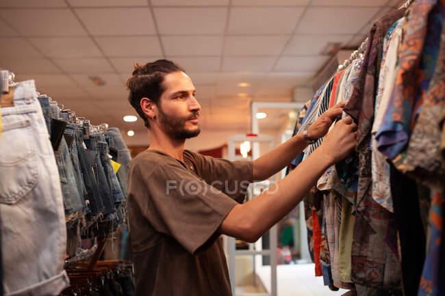 Веселый человек выбирает одежду и аксессуары в магазине — стоковое фото