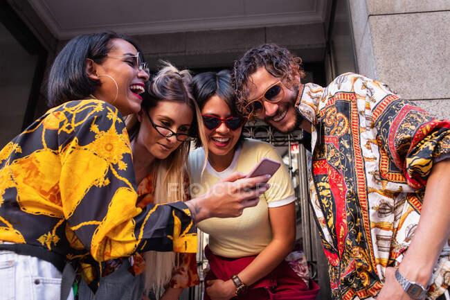 Знизу вистрілив молодий чоловік і жінки в стильному одязі, сміючись і переглядаючи смартфон, стоячи на вулиці разом — стокове фото