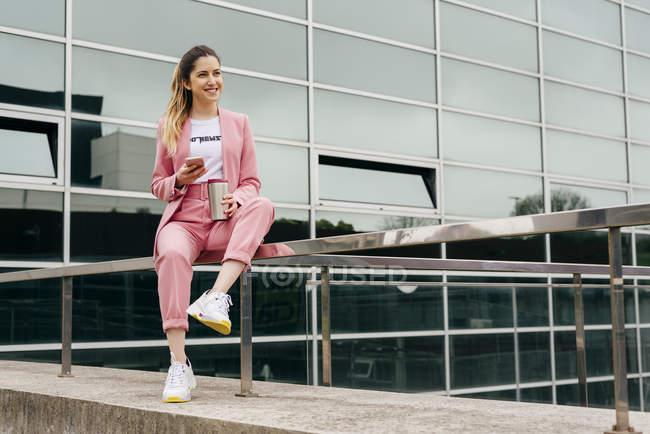 Модні молоді жінки в рожевий костюм з кави і телефон, сидячи на перила перед сучасні Офісні будівлі — стокове фото