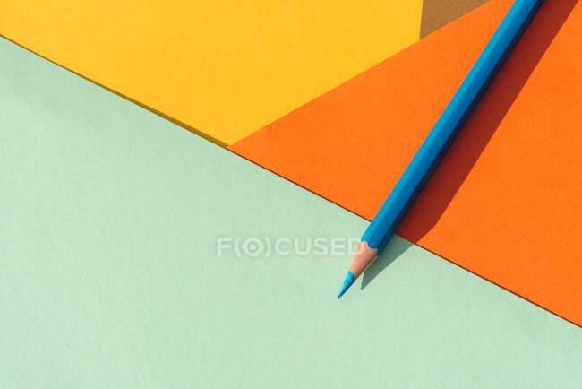 Crayon de couleur, sur fond géométrique bleu clair et orange, concept de retour à l'école — Photo de stock