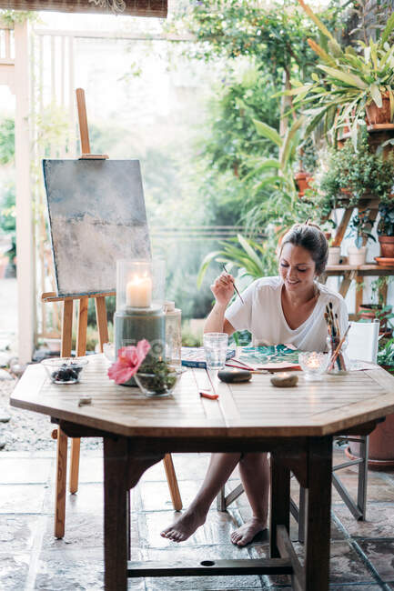 Beautiful female smiling and painting plants while sitting at table in light greenhouse — Stock Photo