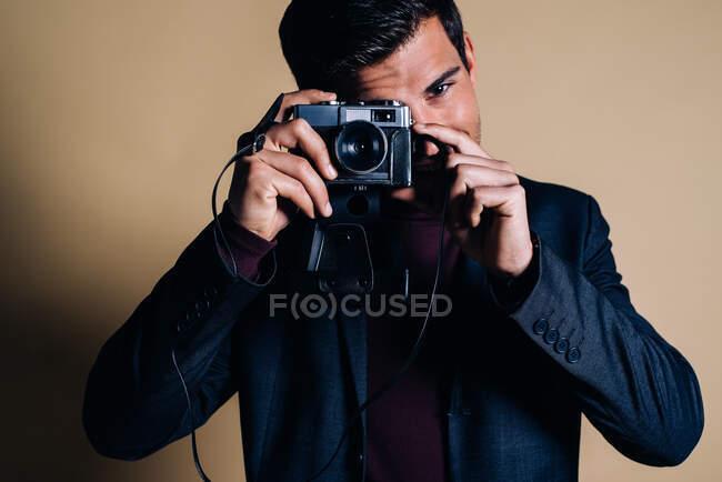 Молодой человек в студии держит винтажную камеру — стоковое фото