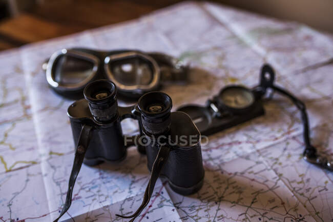Planning a trip on a map with vintage motorcycle glasses, old photo camera, prismatic and compass — Stock Photo