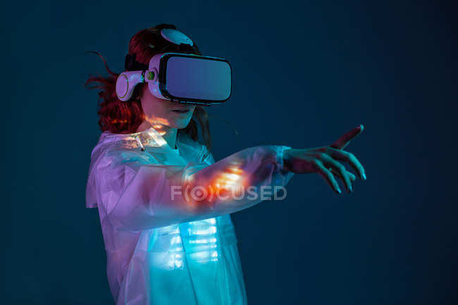 Woman touching air in VR glasses in neon light on blue background — Stock Photo