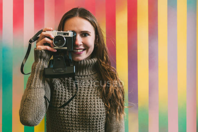 Happy young woman taking photo with vintage camera against colorful background — Stock Photo
