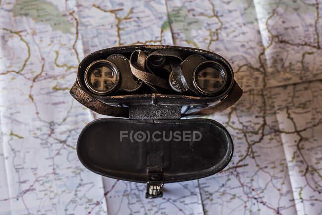 Pianificazione di un viaggio su una mappa con vecchio prismatico — Foto stock