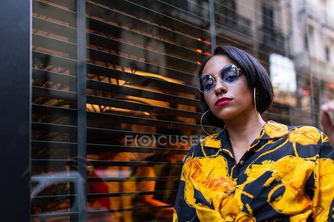 Mujer bastante joven en traje de moda y gafas de sol mirando a la cámara mientras está de pie cerca de la ventana del edificio en la calle de la ciudad - foto de stock