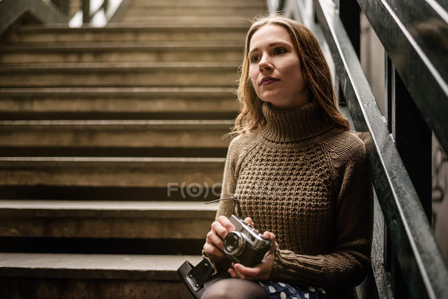 Thoughtful young woman holding vintage camera while leaning on staircase railing — Stock Photo