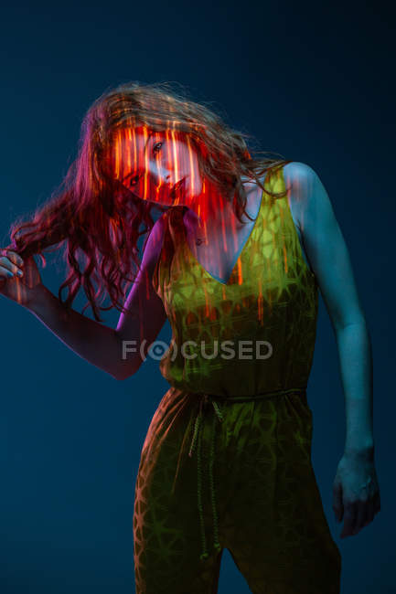 Portrait of sensual young woman posing in stains of neon light — Stock Photo