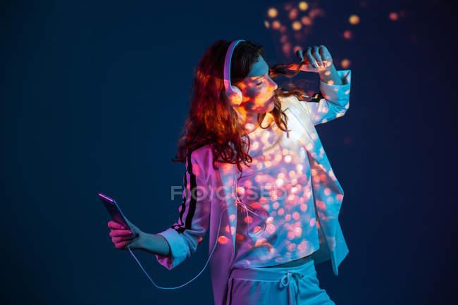 Жінка, танці зі смартфона і навушники в неонові світла — стокове фото