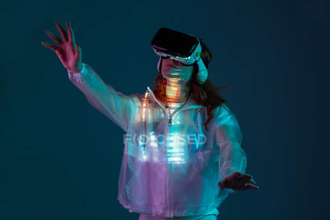 Woman touching air with VR glasses in neon light on blue background — Stock Photo