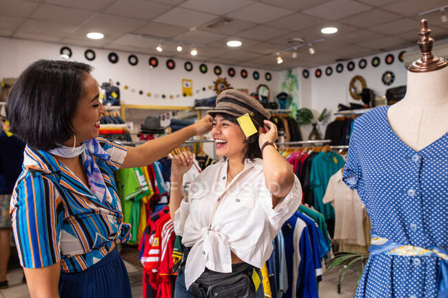 Two lovely women laughing and trying on nice hat while spending time in small store together — Stock Photo