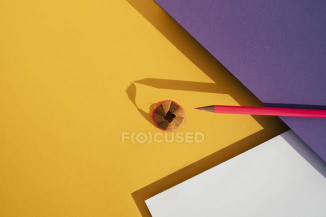 Zurück in die Schule, moderner geomerischer Hintergrund, rosa Bleistift und Späne vom Anspitzen. — Stockfoto