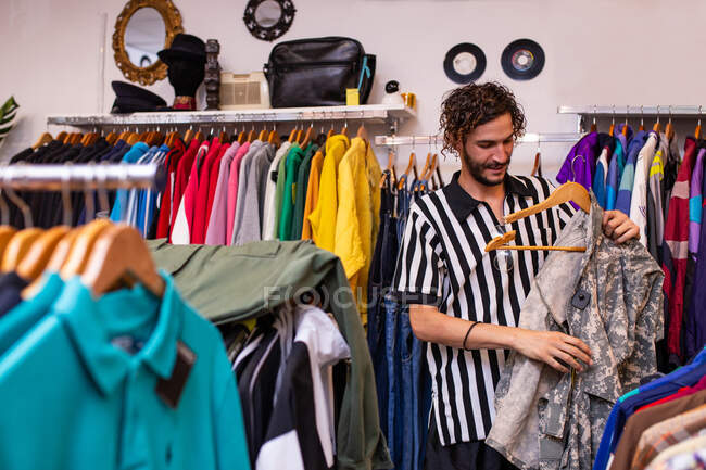 Cheerful man choosing clothing and accessories in shop — Stock Photo