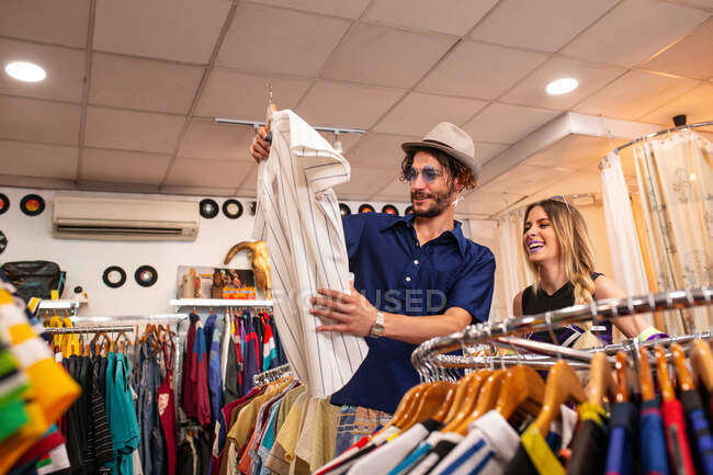 Hombre guapo elegir camisa elegante mientras pasa el tiempo en la pequeña tienda con la novia - foto de stock
