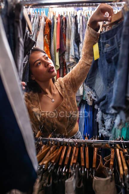 Attraente giovane signora alla ricerca di nuovo vestito su ferrovia vestiti in piccolo negozio — Foto stock