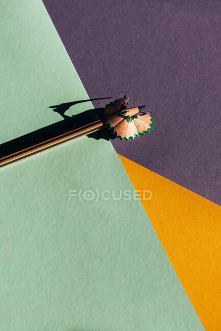 Crayon et copeaux d'affûtage, sur fond de papiers géométriques colorés. Concept de retour à l'école — Photo de stock