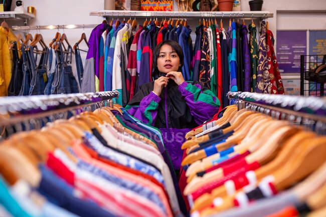 Mulher muito jovem apoiando-se em trilhos de roupas e olhando para a câmera enquanto está de pé em pequena loja — Fotografia de Stock