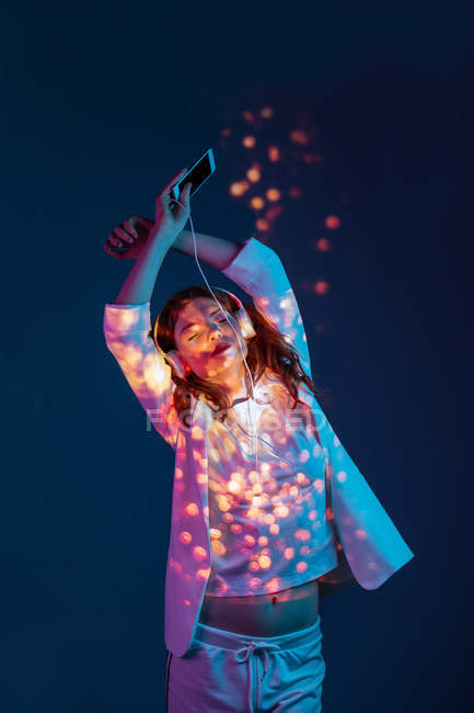 Young woman standing with hands up and eyes closed and enjoying music with smartphone and headphones in light blots — Stock Photo