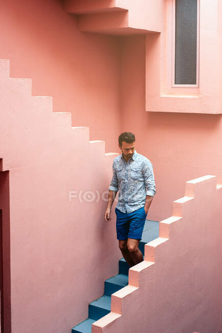 Thoughtful man walking in a pink building stairs — Stock Photo