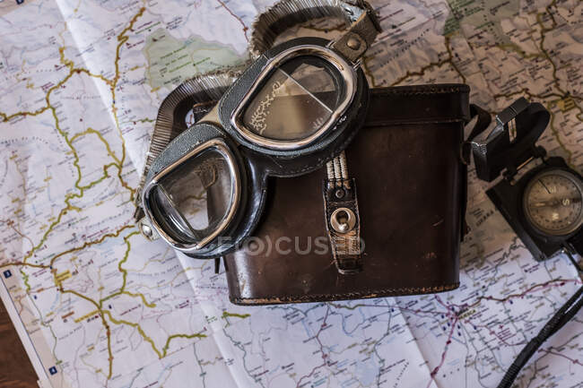 Planning a trip on a map with vintage motorcycle glasses and old prismatic — Stock Photo