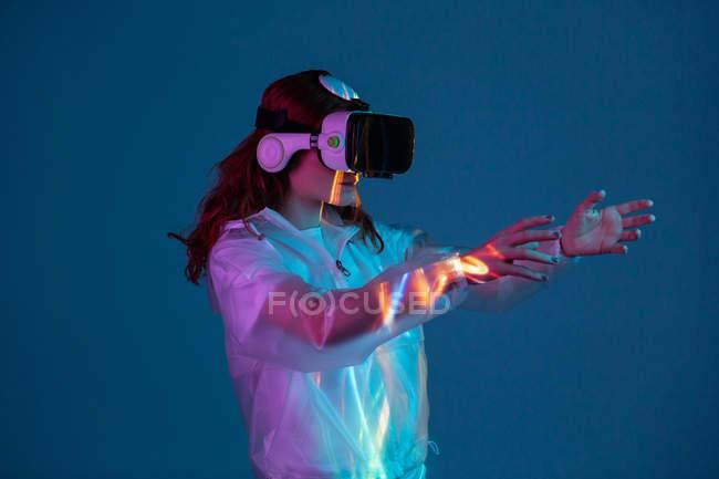 Женщина касается воздуха, имея опыт виртуальной реальности в неоновом свете — стоковое фото