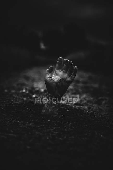 Zombie hand coming out of  ground on dark background — Stock Photo