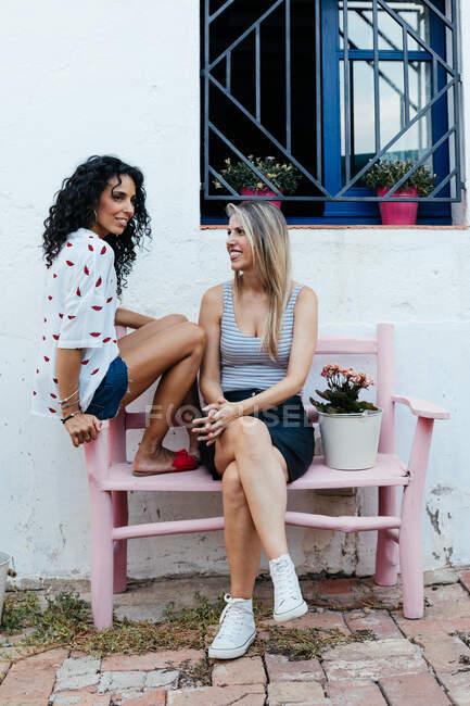Дві дівчинки сидять на лавці на вулиці. — стокове фото