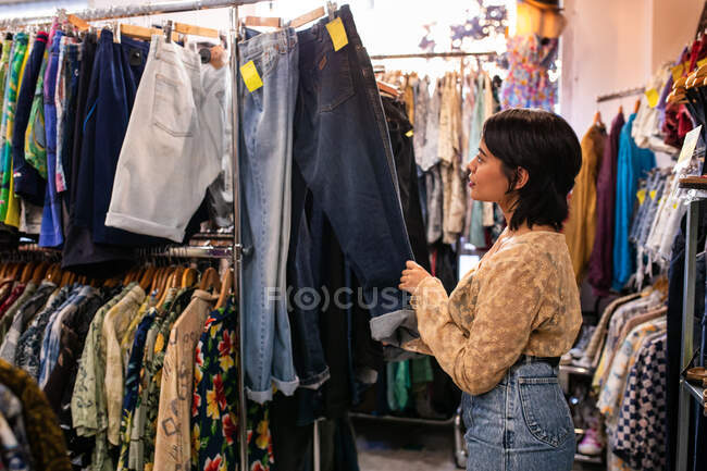 Attractive young lady searching for new outfit on clothes rail in small shop — Stock Photo