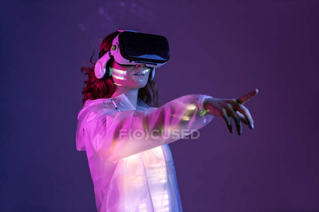 Woman in VR glasses pointing while standing in neon light — Stock Photo