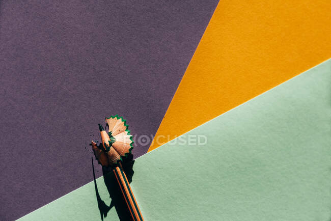 Pencil and shavings from sharpening, on colored geometric papers background. Back to school concept — Stock Photo