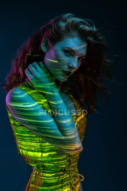 Portrait of sensual woman posing in stripes of warm light — Stock Photo